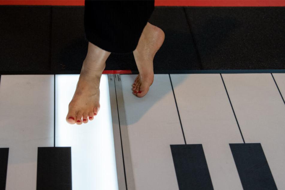 Leslie spielt auf einem begehbaren Klavier mit den Füßen.