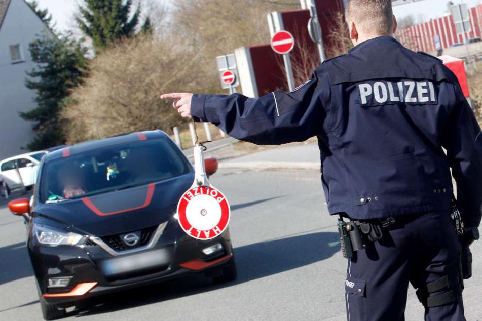 Ein Polizist winkt ein getuntes Auto beim großen Tuning-Treffen in Bochum zur Kontrolle heraus.