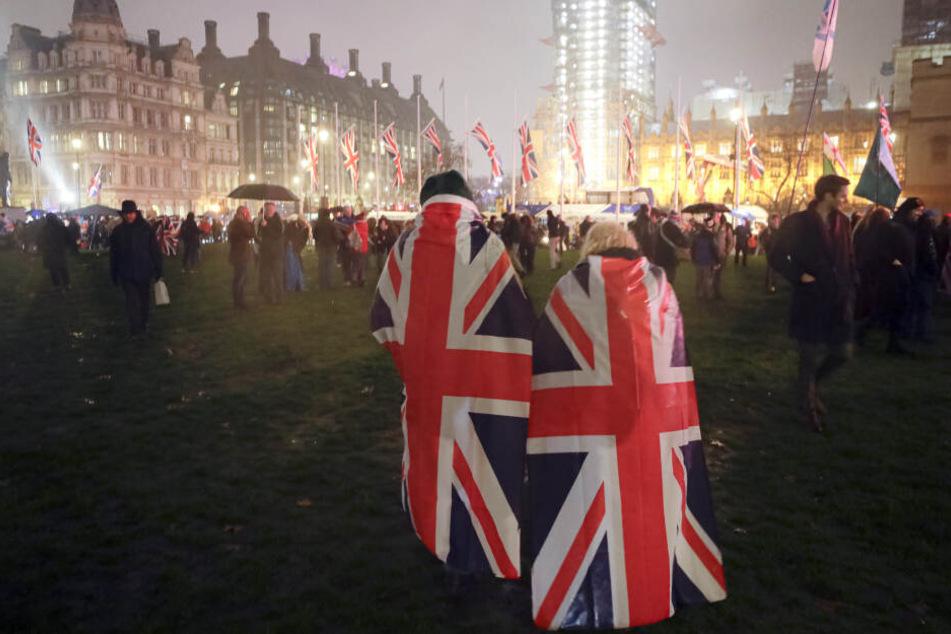 Brexit-Anhänger laufen mit Umhängen, die mit der britischen Nationalflagge bedruckt sind, über den Parliament Square.