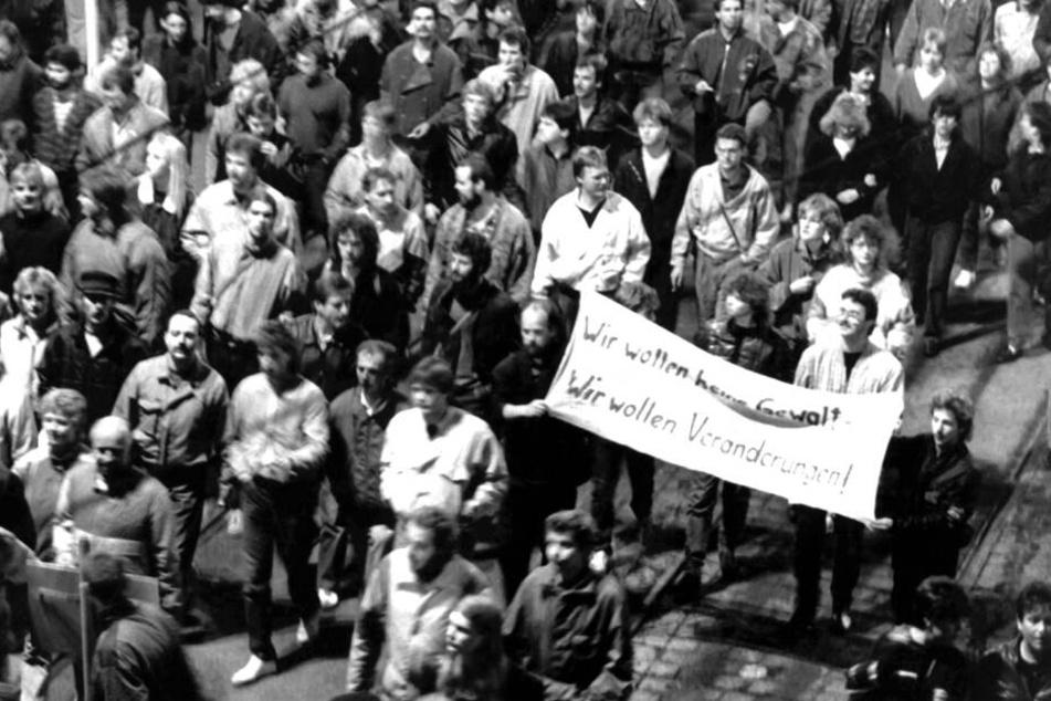 """""""Wir wollen keine Gewalt! Wir wollen Veränderungen!"""" steht auf dem Transparent, das diese Leipziger am 9. Oktober 1989 um den Ring trugen."""