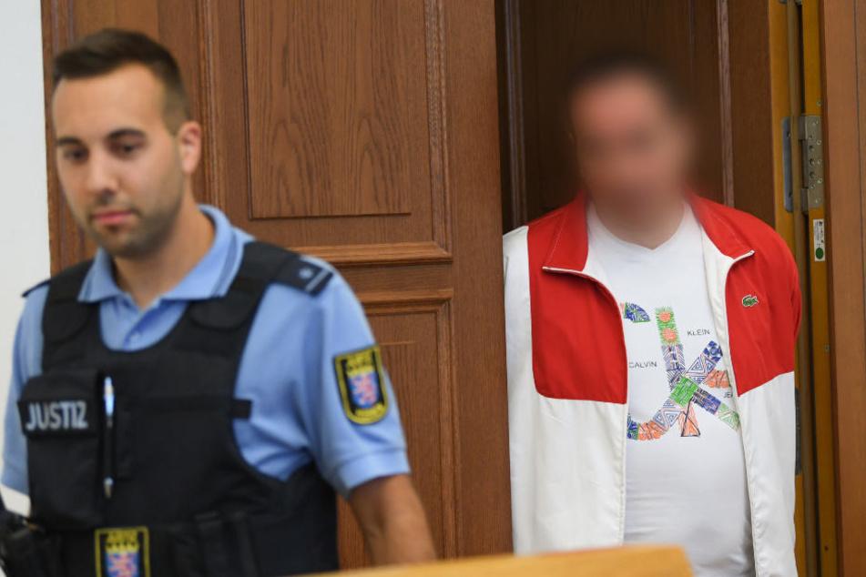 Der Angeklagte betritt in Begleitung eines Justiz-Beamten den Gerichtssaal.