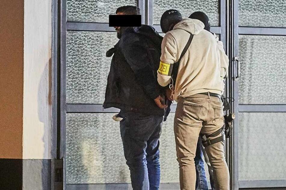 Einem Verdächtigen werden von einem SEK-Beamten Handschellen angelegt.