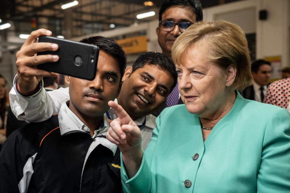 Bundeskanzlerin Angela Merkel (CDU), macht ein Selfie mit Mitarbeitern beim Besuch der Continental Automotive Components India.