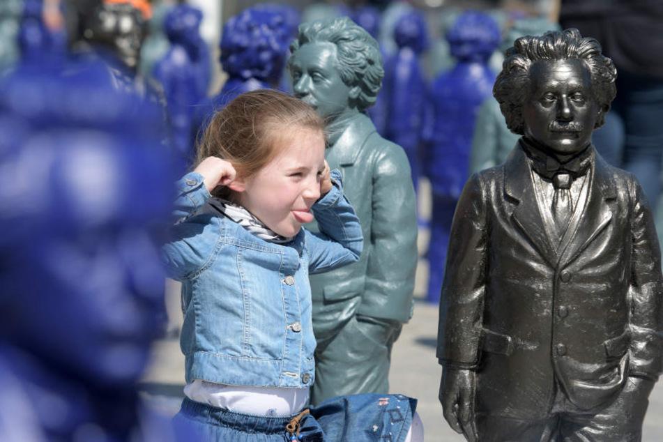 Auf dem Münsterplatz streckt die sechs Jahre alte Isabell Miniaturdarstellungen von Albert Einstein die Zunge heraus.
