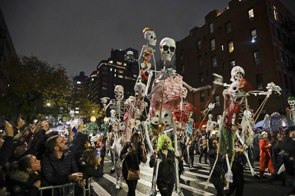 Menschen mit Skelett-Figuren marschieren während der Greenwich Village Halloween-Parade.