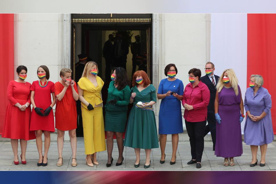 Polens linke Abgeordnete stehen in Regenbogenfarben gekleidet vor dem polnischen Parlament, um während der Vereidigungszeremonie von Präsident Duda (48) ihre Unterstützung für die LGBT-Gemeinschaft auszudrücken.