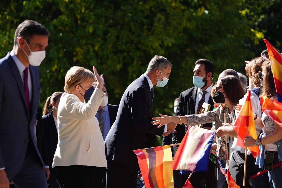 Pedro Sanchez (l-r), Ministerpräsident von Spanien, Angela Merkel und König Felipe VI. begrüßen Schaulustige bei ihrer Ankunft im Kloster von Yuste.