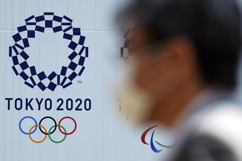 Ein Mann geht mit einem Mundschutz an einem Plakat vorbei, mit dem für die Olympischen Spiele 2020 in Tokio geworben wird.