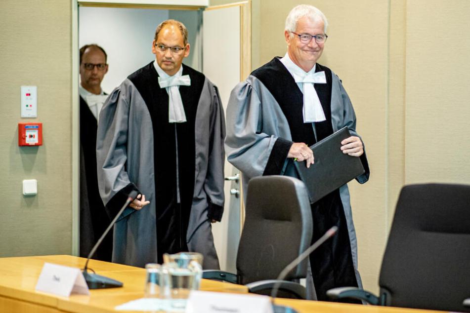 Die Richter Bernhard Flor (von rechts nach links), Christof Brüning und Felix Welti betreten den Gerichtssaal des Landesverfassungsgerichts.