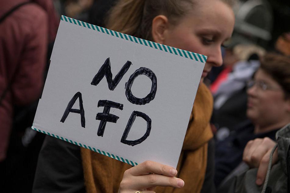 """Eine Demonstrantin hält ein Schild mit der Aufschrift """"No AFD"""" hoch."""