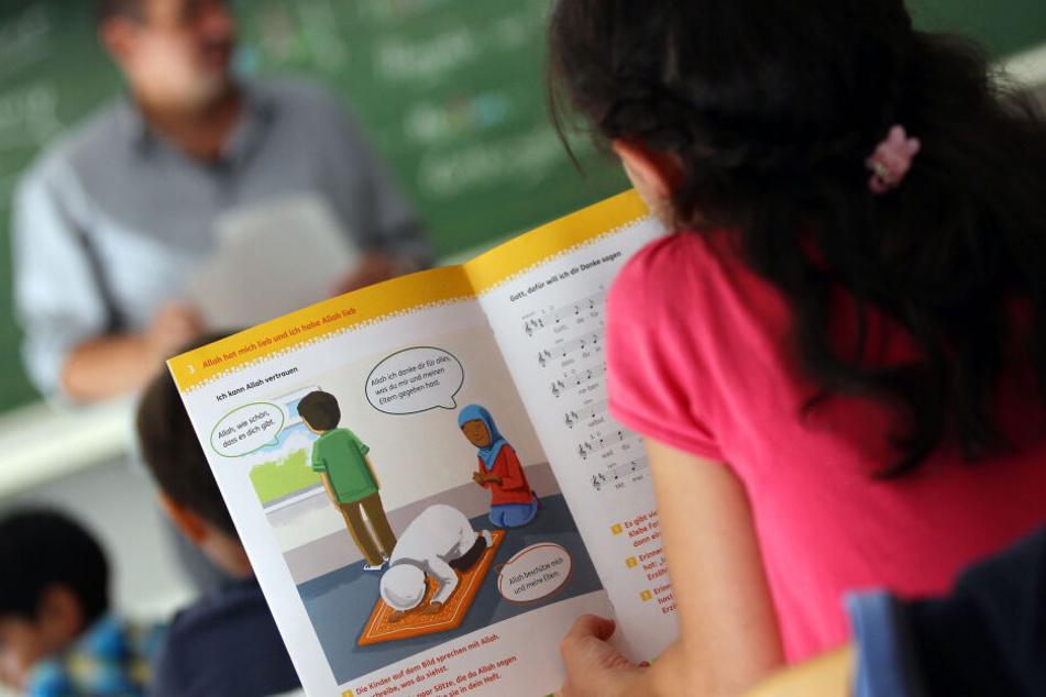 Ein Mädchen liest in einer Schule während des islamischen Religionsunterrichts in einem Schulbuch.