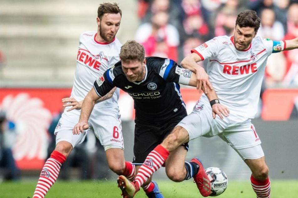 Kölns Marco Höger (l) und Kölns Jonas Hector (r) im Kampf um den Ball mit Bielefelds Fabian Klos.