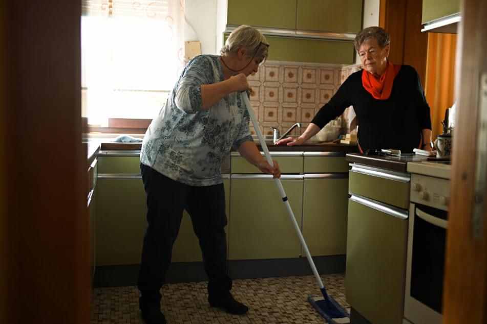 Birgit Bechler (L) hilft der 85-jährigen Frau Fug bei der Hausarbeit.