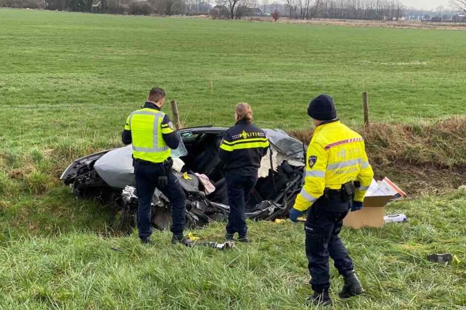 Polizisten untersuchen das Wrack, das am Rande der Autobahn 12 in Richtung Arnheim im Graben liegt.