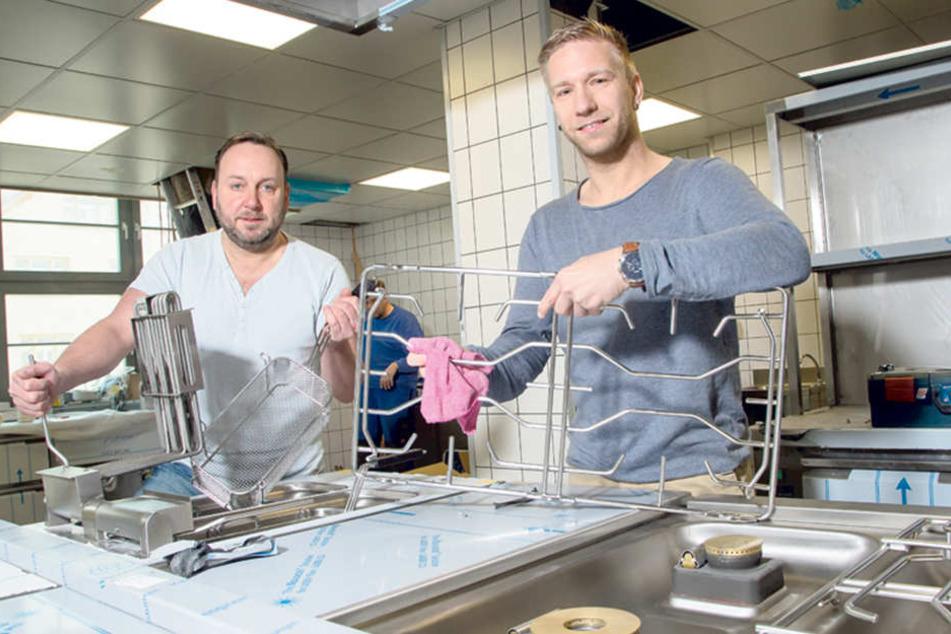 Chefkoch Stephan Kirchner (35) wienert den neuen Gasherd, sein Sous-Chef Karsten Juhrig setzt die Frittierkörbe ein.