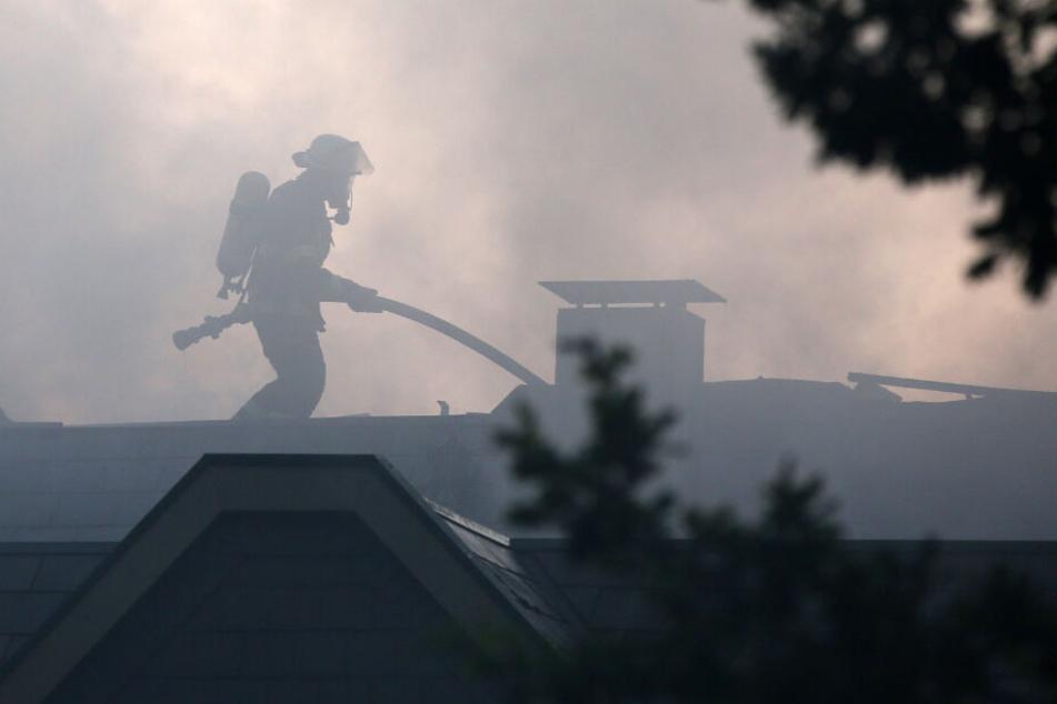 Ein Feuerwehrmann steht auf dem Dach der Anlage und bekämpft den Brand.