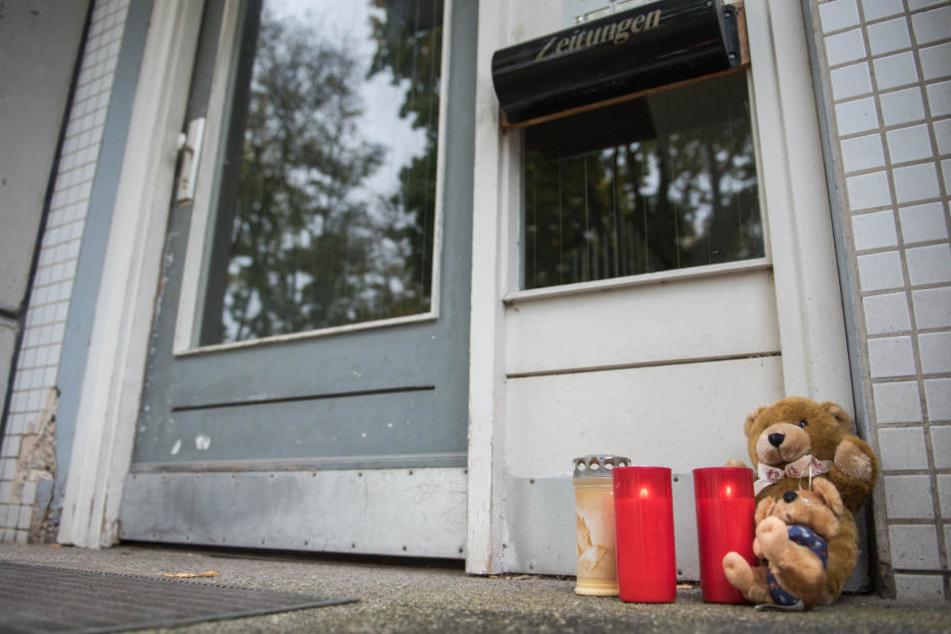 Kerzen und Teddybären aus Stoff stehen vor dem Mehrfamilienhaus: Der Vater muss sich wegen Mord, gefährlicher Körperverletzung, Bedrohung und versuchter Nötigung nun vor dem Gericht verantworten.