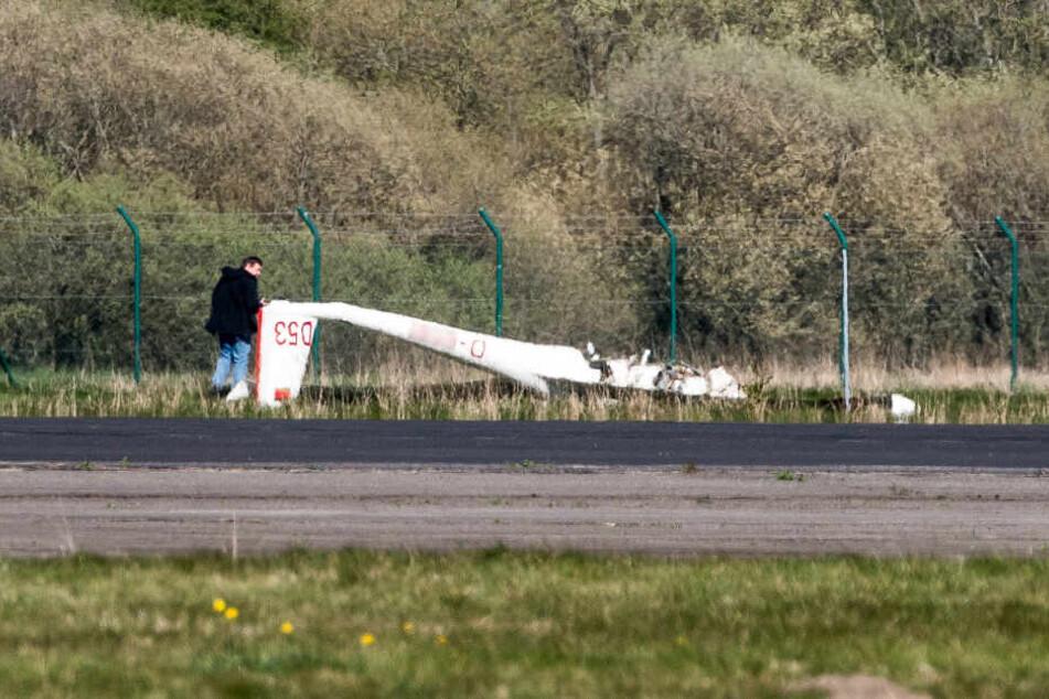 Das Flugzeugwrack liegt auf einem Feld nahe der Landebahn.