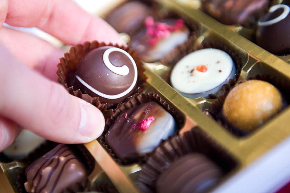 Eine Hand greift nach einer Praline in einer Pralinenschachtel. Mehrere Wochen ohne Süßigkeiten zu leben, finden viele Menschen sinnvoll.
