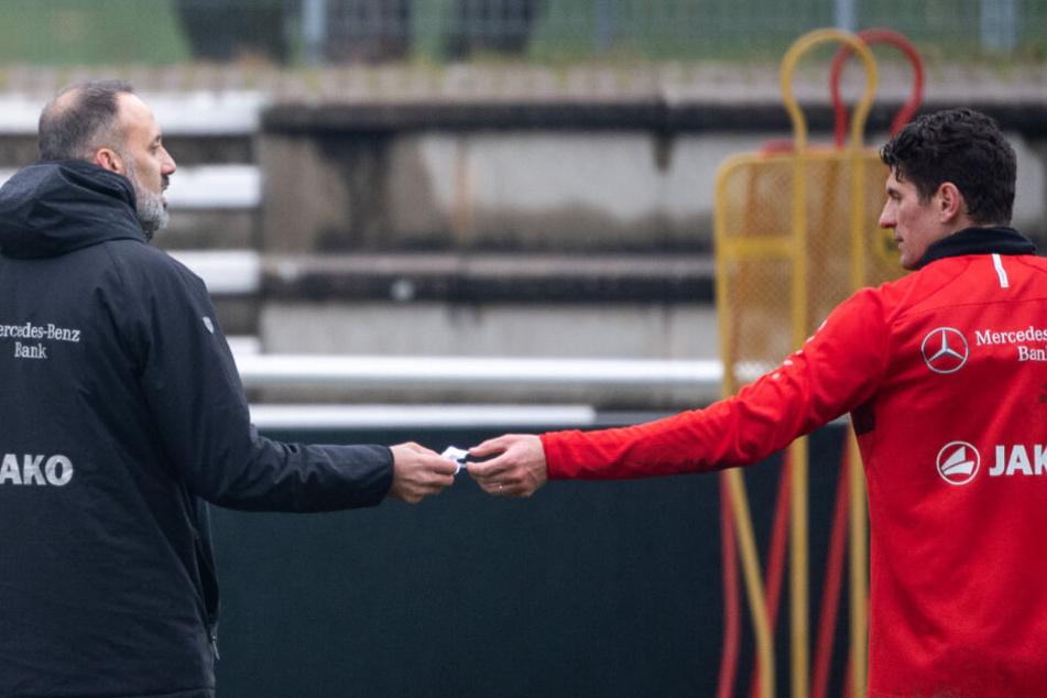Pellegrino Matarazzo (l), Trainer des VfB Stuttgart, nimmt von Mario Gomez einen Zettel entgegen.