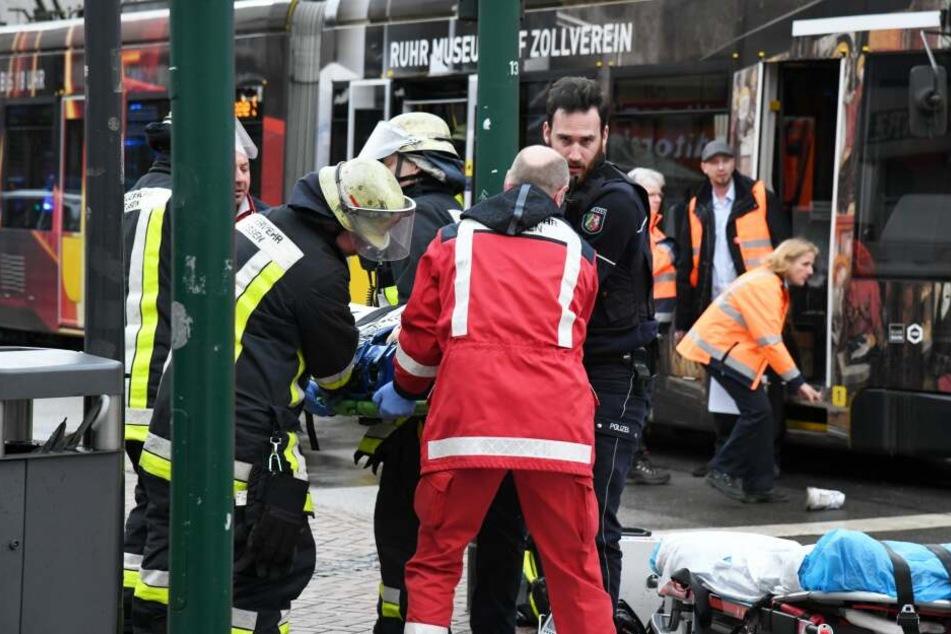Einsatzkräfte versorgen Verletzte, nachdem eine Seniorin an einer Straßenbahn-Haltestelle in eine Menschenmenge gefahren war.