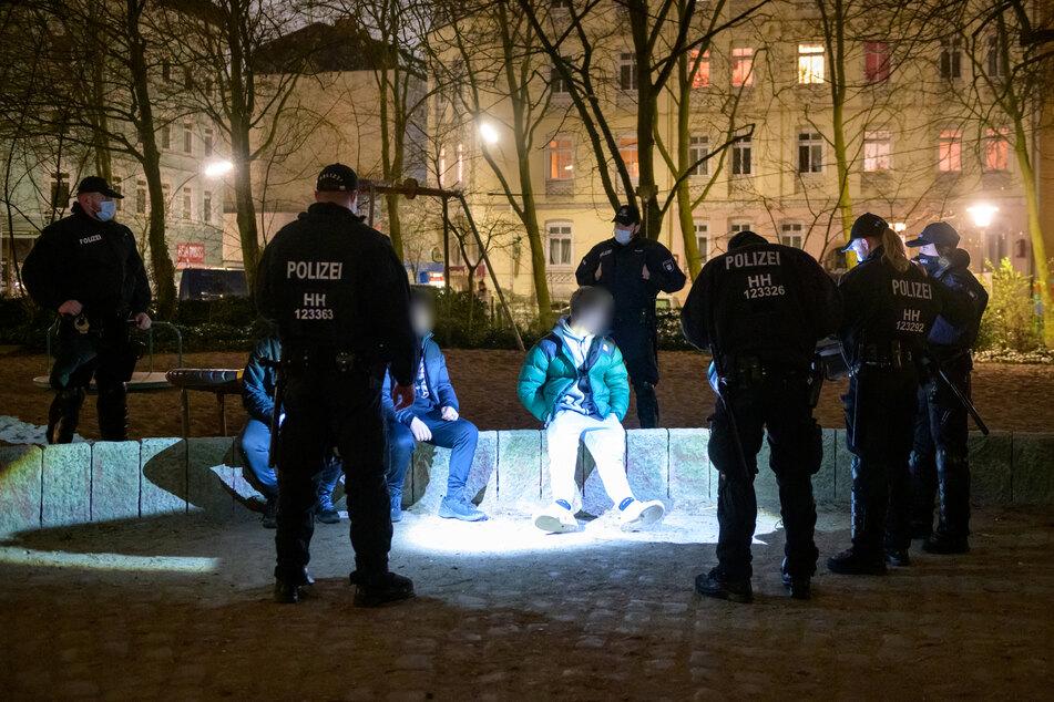 Drei junge Männer werden von Bereitschaftspolizisten auf einem Spielplatz kontrolliert. In Hamburg treten ab Karfreitag zur Bekämpfung der Corona-Pandemie nächtliche Ausgangsbeschränkungen in Kraft.