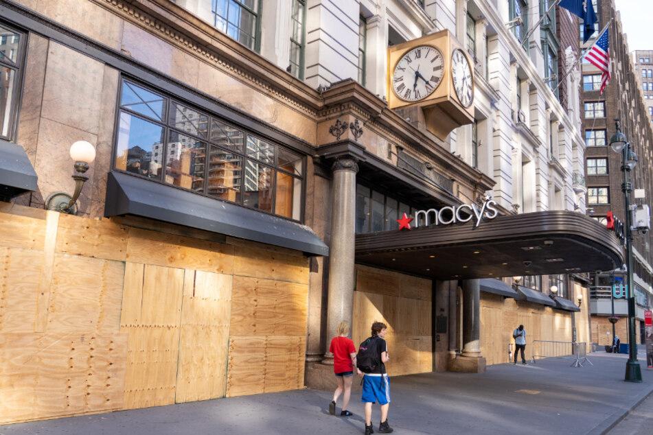 New York: Menschen gehen an einem mit Brettern vernagelten Macy's-Geschäft am Herald Square vorbei.