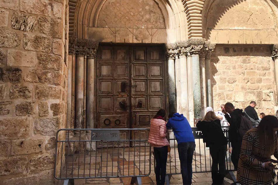 Touristen stehen am 25. Februar 2018 vor der verschlossenen Grabeskirche in Jerusalem.