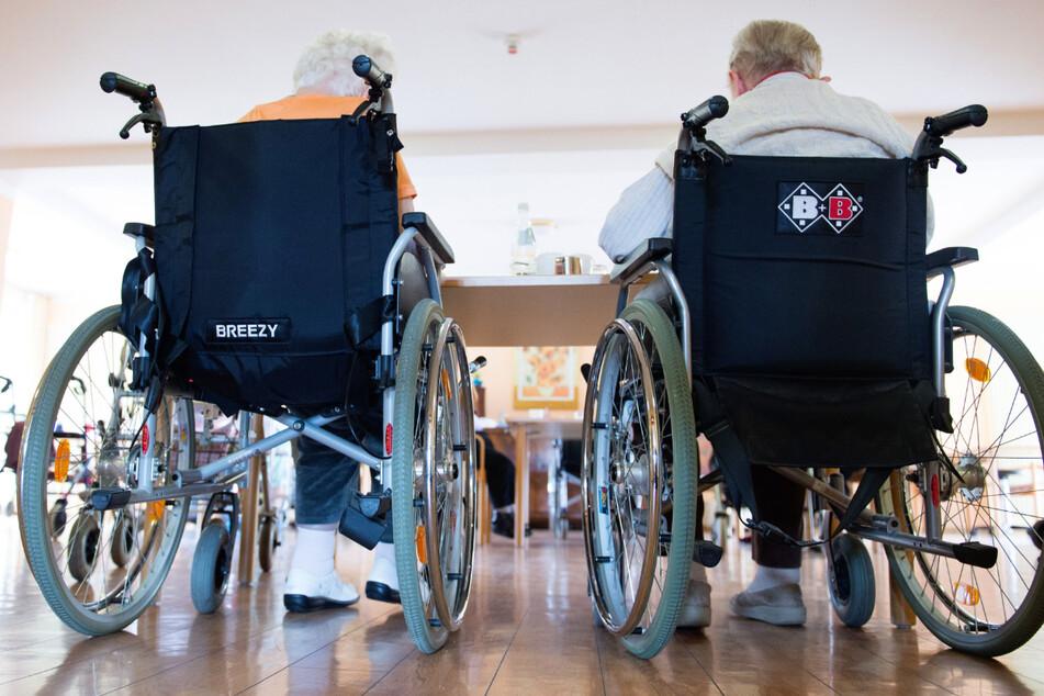 Zwei Frauen sitzen in einem Pflegeheim in ihren Rollstühlen nebeneinander. Nachdem viele Pflegeheimbewohner gegen das Coronavirus geimpft sind, plant die baden-württembergische Landesregierung einem Bericht zufolge Lockerungen für Besucher. (Symbolbild)
