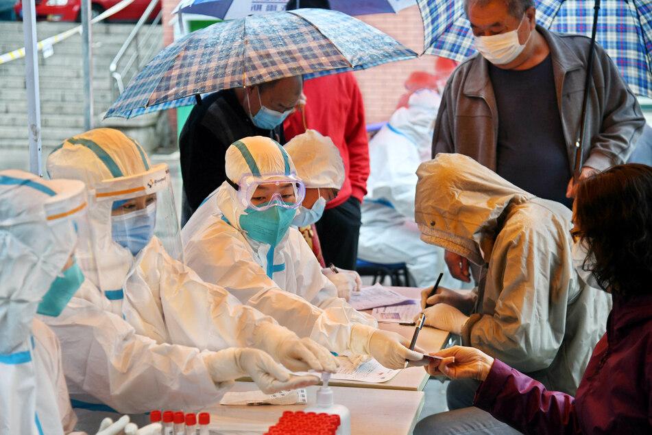 Anwohner melden sich für COVID-19-Tests an einem Testpunkt im Distrikt Shibei.