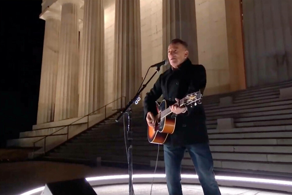 Bruce Springsteen sings and strums his guitar alone in front of the Lincoln Memorial.