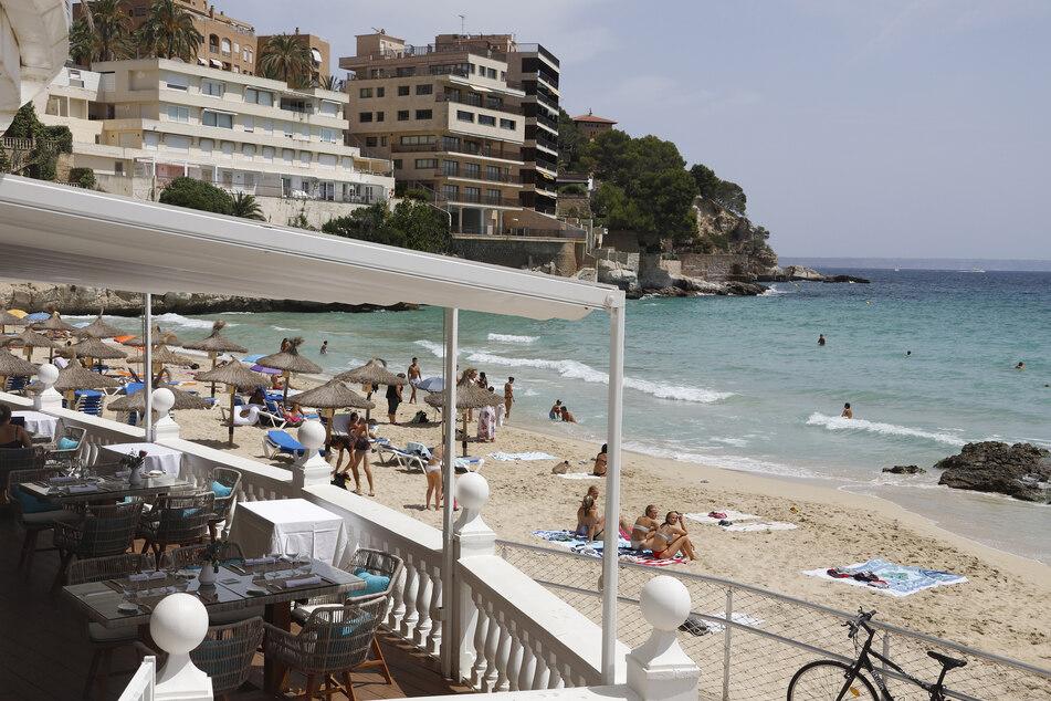 Menschen genießen die Sonne am Strand von Cala Major auf Mallorca. Für deutsche Urlauber gilt nach einem Ausflug auf die Balearen neuerdings Testpflicht.