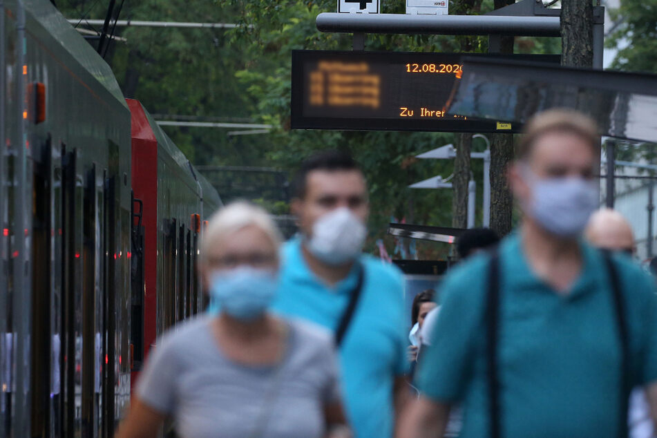 Fahrgäste verlassen eine Straßenbahn und tragen Mundschutz.