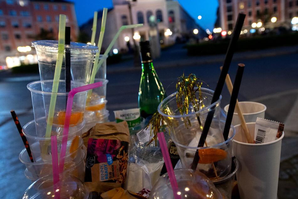 Zahlreiche Plastikbecker und Müll sind am Abend in einem übervollen Mülleimer am Gärtnerplatz zu sehen. Die Stadt will die Lage dort und in der Türkenstraße entspannen, indem die Ludwigsstraße an Wochenenden für Feiernde gesperrt wird.