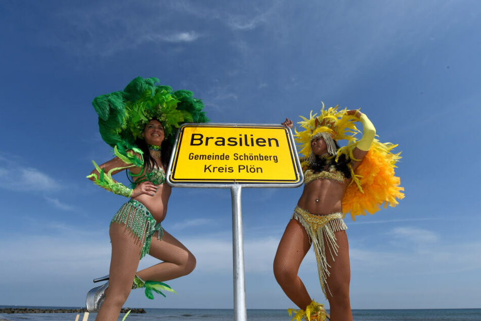 Die brasilianische Tänzerinnen Luciana (links) und Simone stehen neben dem Ortsschild von Brasilien am Ostseestrand. Der Strandabschnitt in der Gemeinde Schönberg ist einer von vielen Ortsnamen in Schleswig-Holstein, die nach weiter Welt klingen.