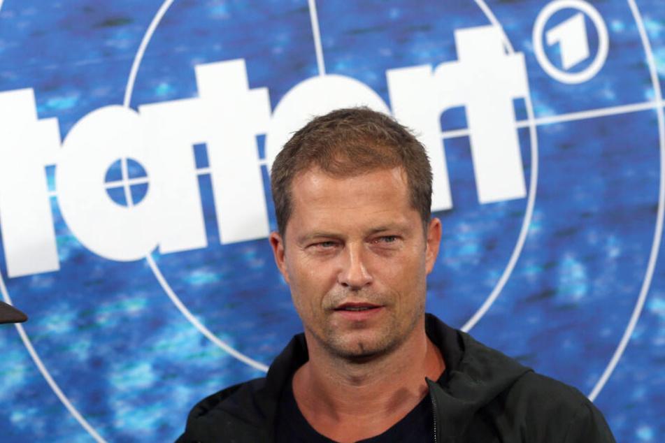 """Der Schauspieler Til Schweiger steht vor einer Stellwand mit dem """"Tatort""""-Logo."""