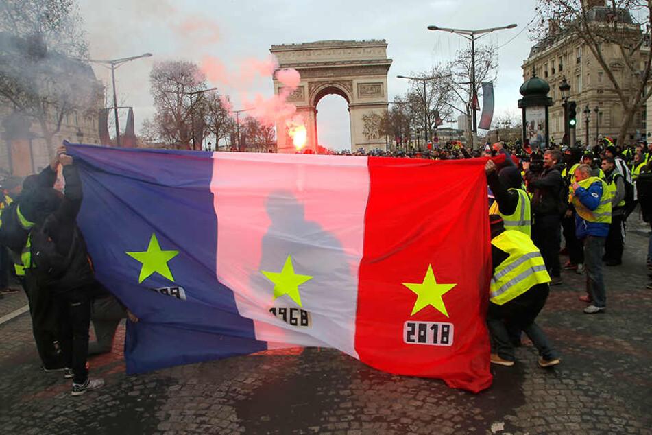 """Demonstranten der """"Gilets Jaunes"""", also der """"Gelbwesten"""", halten eine französische Fahne, im Hintergrund ist der Triumphbogen zu sehen."""