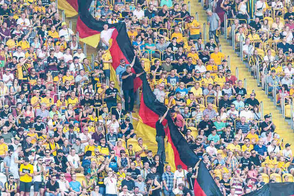 Dynamo-Fans halten im Stadion mehrere Deutschland-Fahnen hoch.