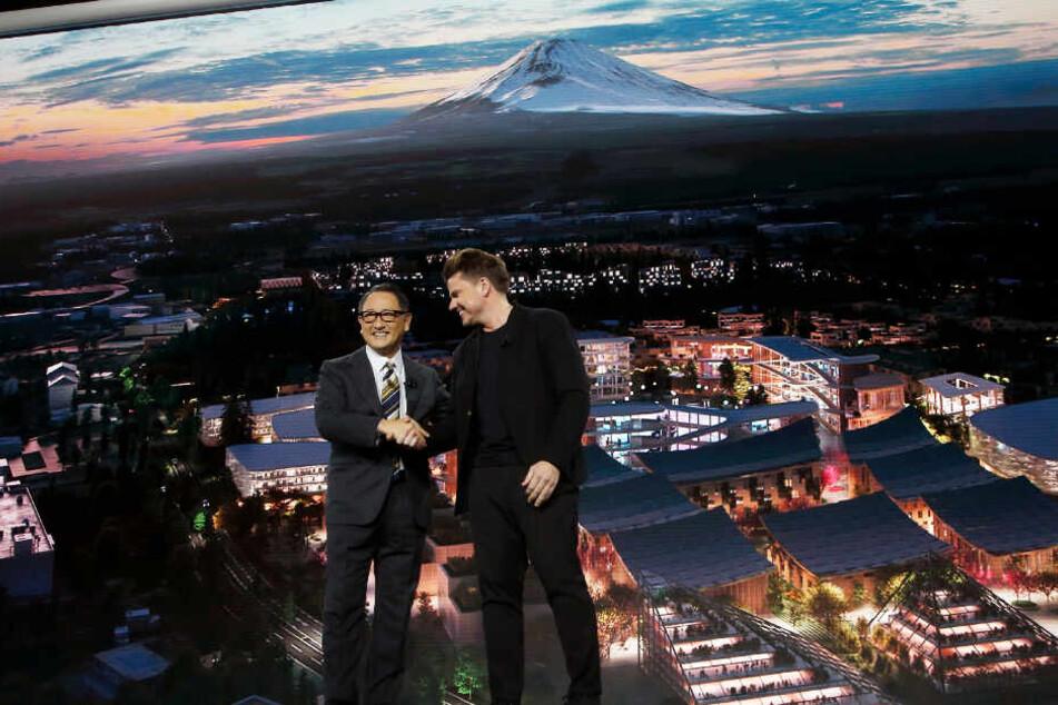 Akio Toyoda (l), Firmenchef von Toyota, und der Architekt Bjarke Ingels planen die Stadt der Zukunft.
