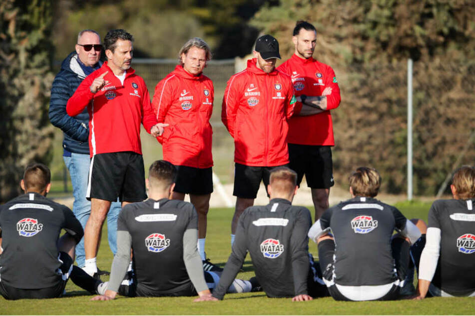 Dirk Schuster bei einer Ansprache an seine Mannschaft. Auch Aue-Boss Helge Leonhardt (hinten) hört interessiert zu.