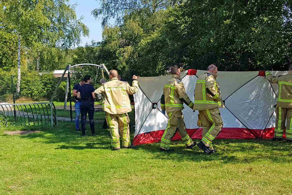 Rettungskräfte stellen eine mobile Absperrwand an einem Spielplatz auf, auf dem der Mann getötet wurde.