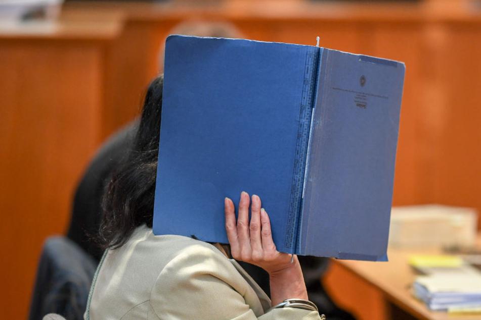 Die 49-Jährige Angeklagte hält sich zu Prozessbeginn eine Akte vor das Gesicht. (Archiv)