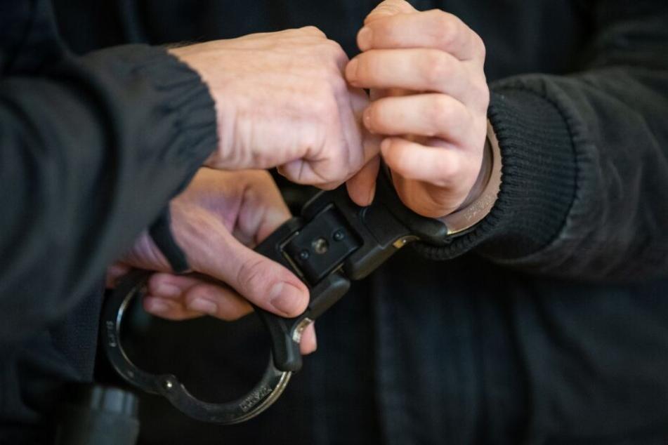Im Gerichtssaal werden dem Angeklagten die Handschellen abgenommen.