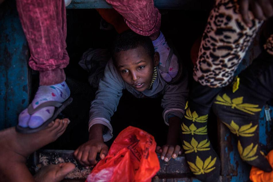 Ein Flüchtlingskind aus Eritrea versucht, an Bord eines überfüllten Holzbootes zu klettern, das auf Hilfe durch das spanische Rettungsschiff von Open Arms wartet.