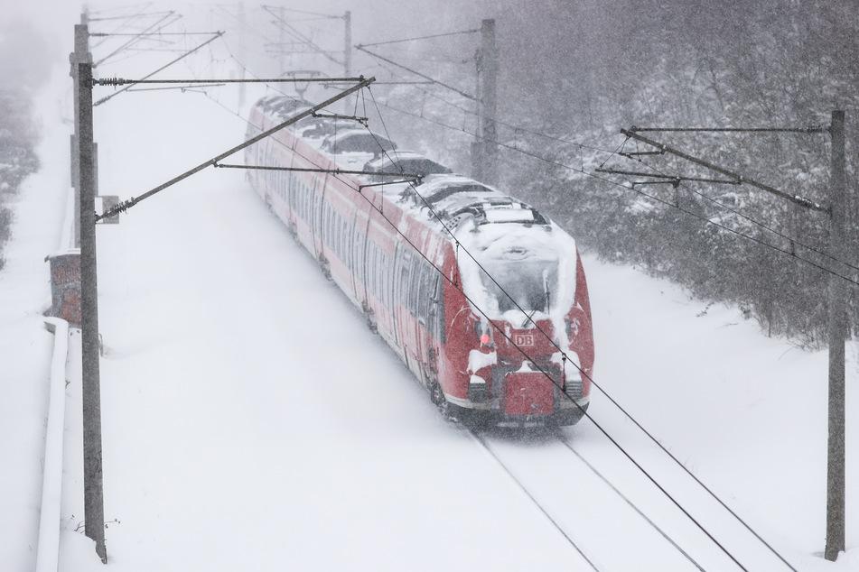 Eine Bahn fährt über verschneite Gleise.