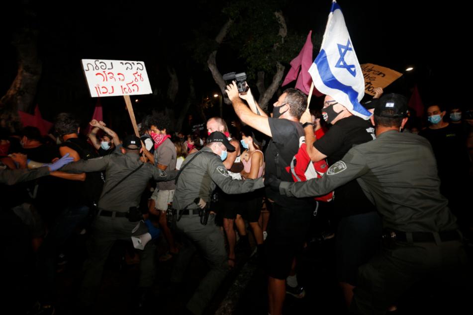 Tel Aviv: Polizisten stoßen mit Demonstranten zusammen, die trotz eines landesweiten Lockdowns aufgrund der Corona-Pandemie gegen den Premierminister Netanjahu protestieren.