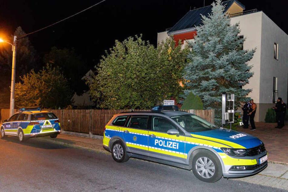 Man sieht die Polizisten, wie sie um das Mehrfamilienhaus postiert sind.