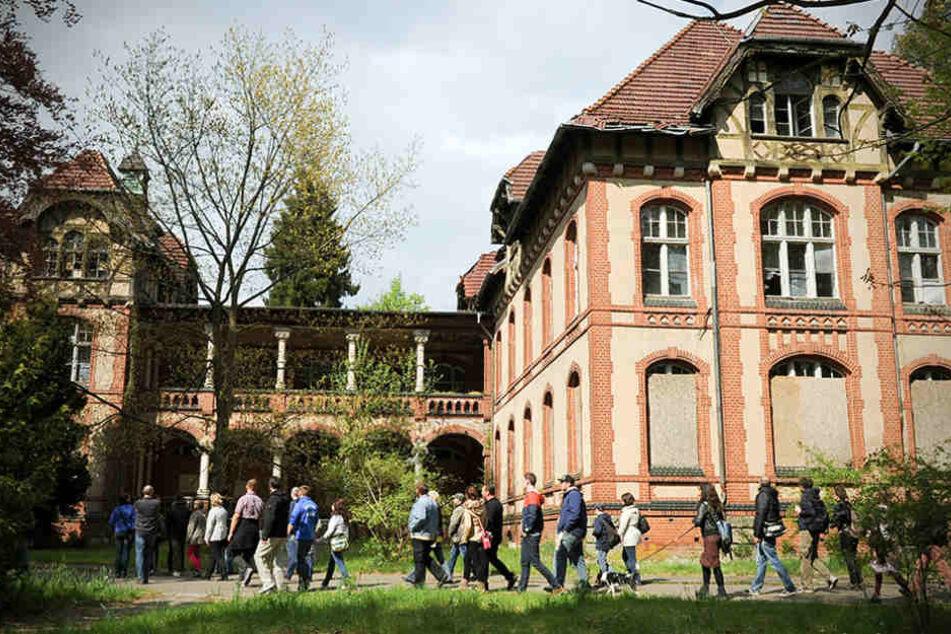 Eine Besuchergruppe geht an der ehemaligen Chirurgie auf dem Gelände der Beelitz-Heilstätten in Beelitz (Brandenburg) entlang.