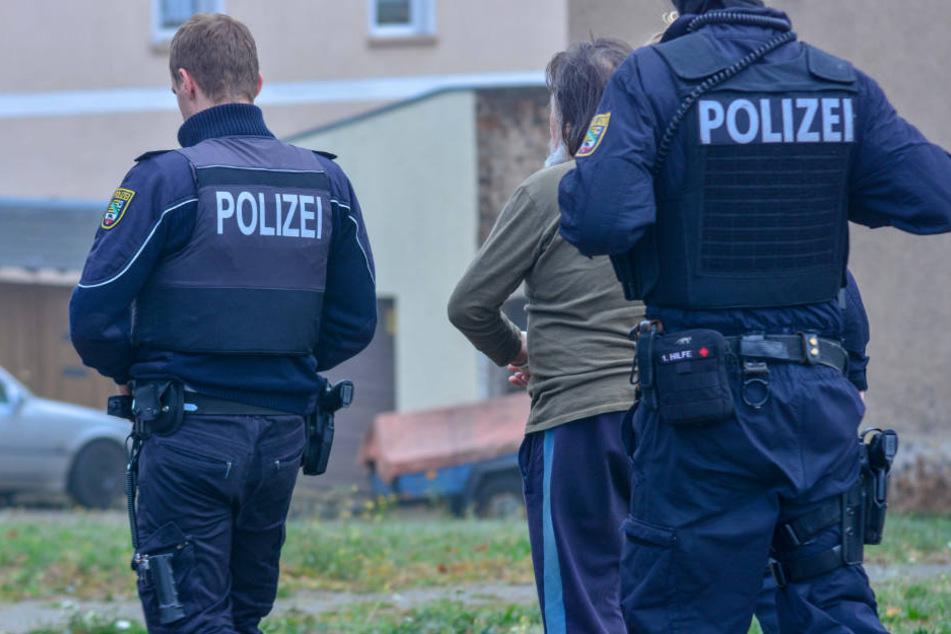 Der Vater des Hauptverdächtigen wird abgeführt.