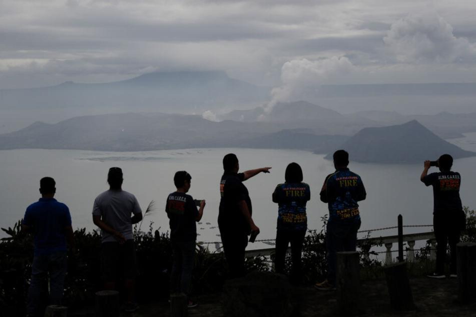 """Leute schauen auf den Vulkan """"Taal"""" in Tagaytay, aus dem eine Wolke aufsteigt."""